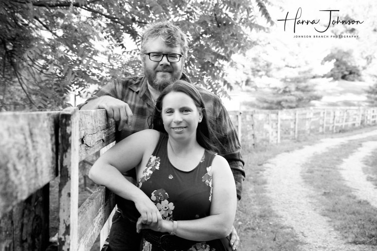 Black and white engagement photo with horse fence in barn lot in cynthiana Kentucky